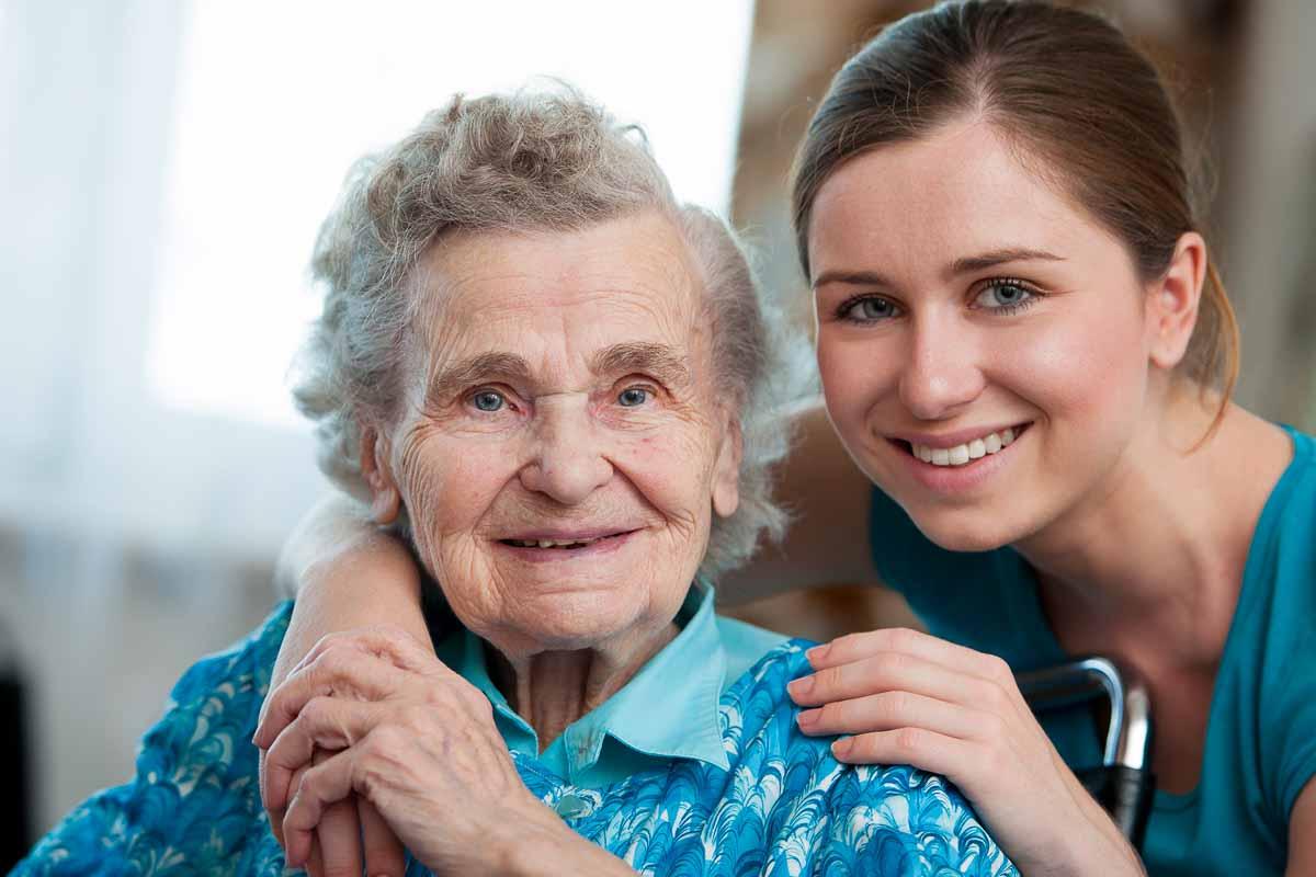 Pflegefachkraft betreut liebevoll ältere Frau