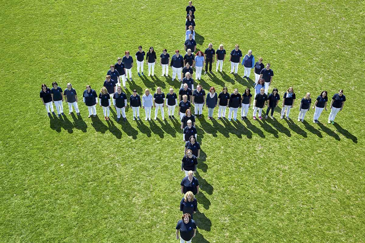 Mitarbeiter der Evangelischen Sozialstation Mosbach stellen das Logo der Diakonie nach